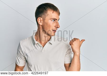 Young caucasian man wearing casual white polo pointing thumb up to the side smiling happy with open mouth