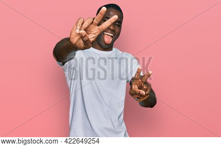 Young african american man wearing casual white t shirt smiling with tongue out showing fingers of both hands doing victory sign. number two.