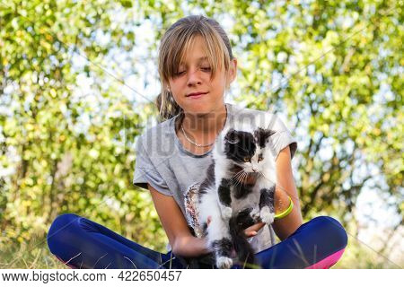 Defocus Blonde Little Girl Holding And Caress Cat, Black And White Small Beautiful Kitten. Nature Gr
