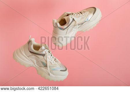 White Sneakers Fly. Female White Leather Shoes On Pink Background. Pair Of Stylish Urban Sneakers. C