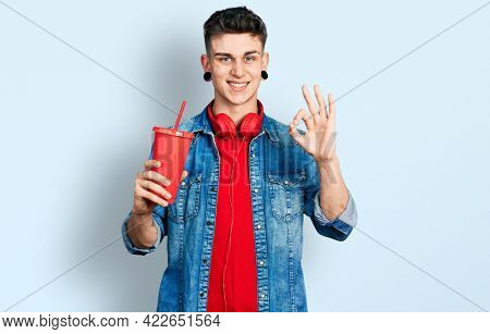 Young caucasian boy with ears dilation drinking glass of cola beverage doing ok sign with fingers, smiling friendly gesturing excellent symbol