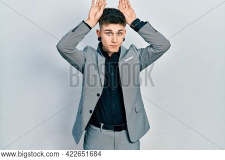 Young caucasian boy with ears dilation wearing business jacket doing bunny ears gesture with hands palms looking cynical and skeptical. easter rabbit concept.