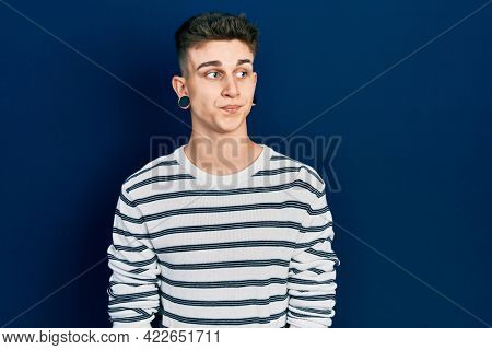 Young caucasian boy with ears dilation wearing casual striped shirt smiling looking to the side and staring away thinking.