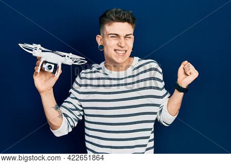 Young caucasian boy with ears dilation holding drone screaming proud, celebrating victory and success very excited with raised arm