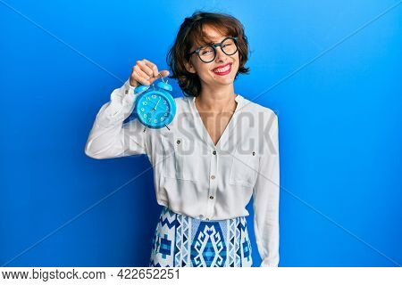 Young brunette woman holding alarm clock looking positive and happy standing and smiling with a confident smile showing teeth