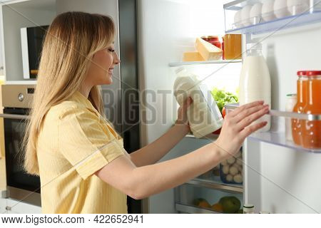 Young Woman Putting Gallon Of Milk Into Refrigerator In Kitchen
