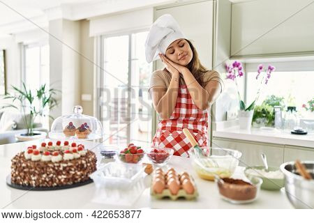 Beautiful young brunette pastry chef woman cooking pastries at the kitchen sleeping tired dreaming and posing with hands together while smiling with closed eyes.