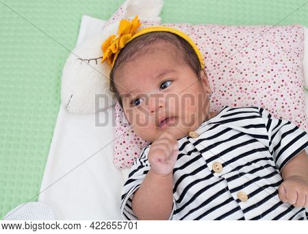 Newborn Baby Girl Lying Down And Playing Alone With Cute Yellow Headband Wearing On.