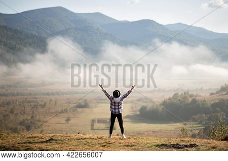Happy Girl Standing On Top Of Mountains With Raised Arms And Enjoy Amazing The View. Silhouette Fema