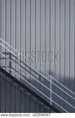 Metal Stair And Banister On Gray Corrugated Steel Wall Of Warehouse Building In Incomplete Construct
