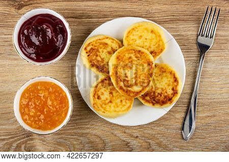 White Bowls With Cherry Jam, Orange Jam, White Plate With Cottage Cheese Pancakes, Fork On Brown Woo