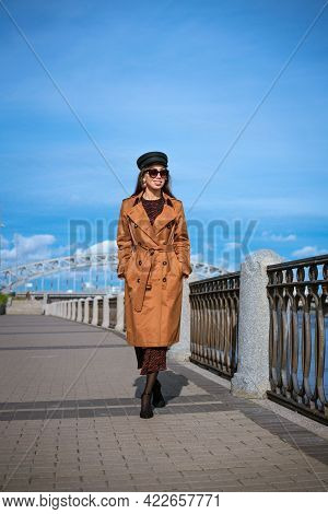 Beautiful Caucasian Woman In Sunglasses, In A Black Cap And Jacket Posing While Standing On The Emba