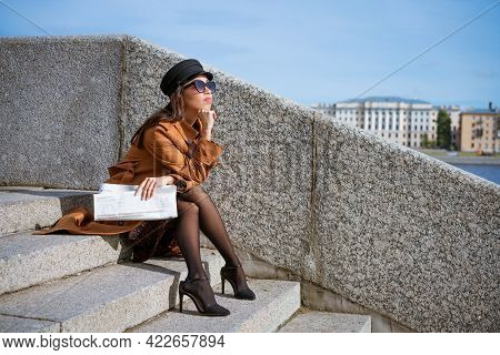 Young Woman In Sunglasses Of Caucasian Ethnicity Sits On The Steps On The Embankment In A Black Cap