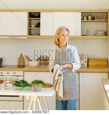 Beautiful Senior Woman In Kitchen Apron Wiping Hands During Cooking, Looking In Window With Smile An