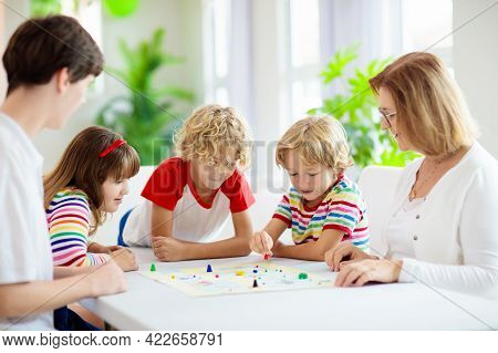 Family Playing Board Game At Home. Kids Play Strategic Game. Little Boy Throwing Dice. Fun Indoor Ac