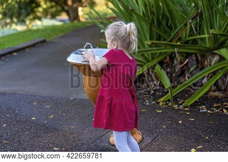 Mackay, Queensland, Australia - June 2021: Young Female Child Drinking From A Water Fountain In The