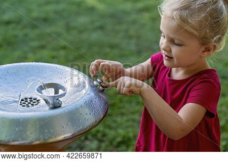 Mackay, Queensland, Australia - June 2021: Young Girl Presses The Button On A Drinking Fountain In A