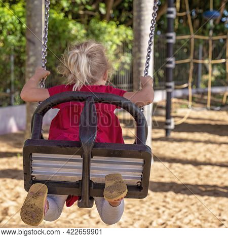 Mackay, Queensland, Australia - June 2021: Focus On The Swing As A Young Girl Child Rides In A Playg