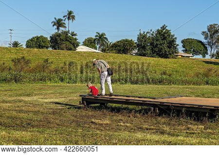 Mackay, Queensland, Australia - June 2021: A Little Girl And Her Grandfather Exploring What's At The