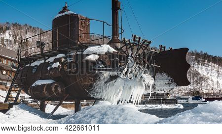 An Old Rusty Submarine Stands On The Banks Of The River. There Is Snow And Fancy Icicles On The Body