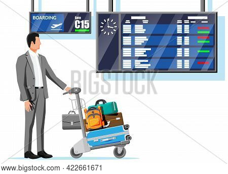 Man And Hand Truck Full Of Bags In Terminal. Departure Arrival Timetable. Airport Luggage Trolley. H