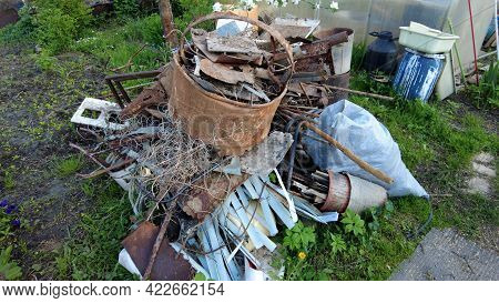 Litter On Land Plot. Garbage Pile With Iron And Plastic On The Grass. Heap With Old Rusty Iron, Tank