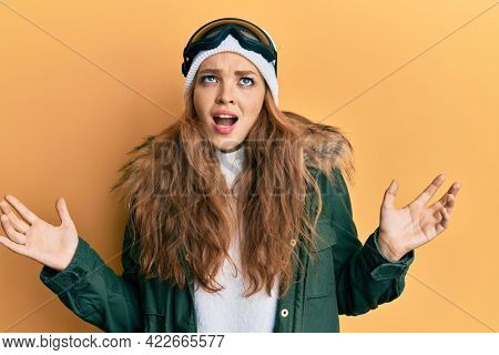 Beautiful blonde caucasian woman wearing snow wear and sky glasses crazy and mad shouting and yelling with aggressive expression and arms raised. frustration concept.