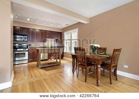 Kitchen in condo with cherry wood cabinetry and eating area