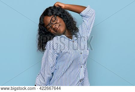 Beautiful african young woman wearing casual clothes and glasses stretching back, tired and relaxed, sleepy and yawning for early morning