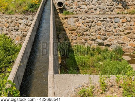 Water Flowing In Irrigation Aqueduct With Stone Wall In Background.