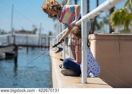 Children Fishing. Couple Of Kids On Pier. Child At Jetty With Rod. Boy And Girl With Fish-rod.
