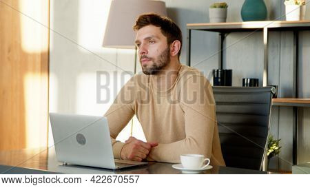 Young thinking male with laptop at remote work