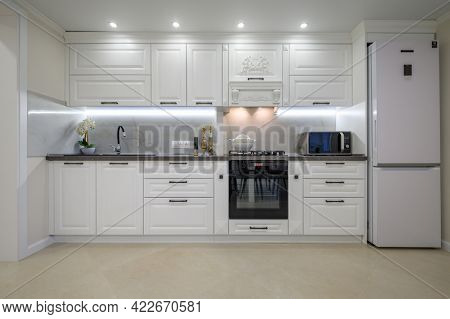 Modern large luxurious white kitchen interior, whole front view