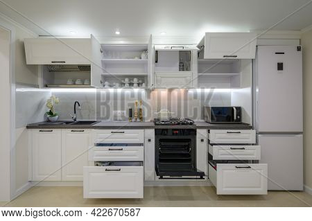 Modern large luxurious white kitchen interior, some drawers pulled out, front view