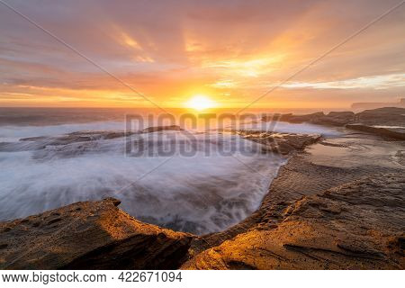Sunrays Burst Forth From Sunrise Sun On Beautiful Coastline And Colouring Clouds In Teh Sky With Wav