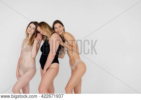 Smiling Multicultural Girls In Lingerie Hugging While Posing At Camera Isolated On White, Body Posit