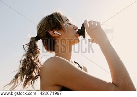 Athletic woman using earphones and drinking water