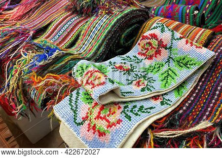 Close Up Of Ukrainian Clothes - Traditional Embroidered Shirts And Beaded Belts. Secondhand Goods On