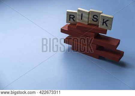 Risk Concept With Alphabet Of Risk On Unstable Structure Of Red Wooden Domino On Blue Background.