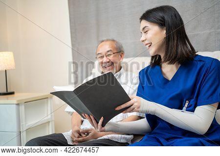 Asian Young Woman Nurse At Nursing Home Taking Care Of Senior Elderly Man Sit On Sofa. Caregiver The