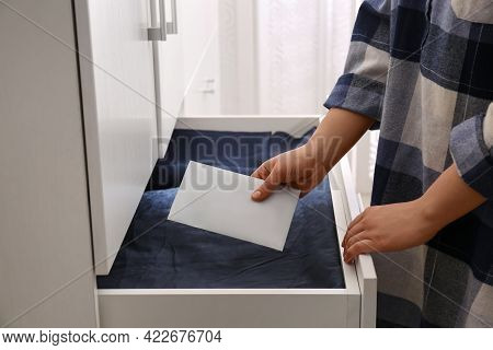 Woman Putting Scented Sachet Into Drawer With Linens, Closeup