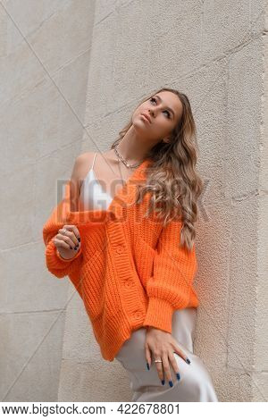 Portrait Of Fashionable Women In Orange Sweater And Beige Sweater Posing In The Street