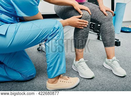 Osteopath Doing A Diagnosis Of A Womans Knee At A Rehabilitation Center, Close-up. Patient With Knee