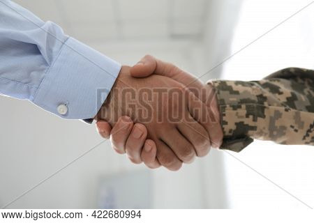 Soldier And Businessman Shaking Hands Indoors, Closeup
