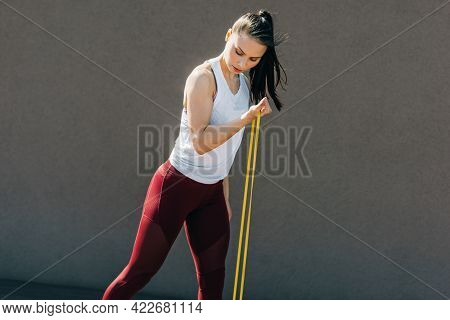 Young Sporty Woman Exercising With Resistance Band On A Sunny Day. Athlete Female Working Out With E