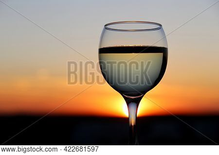 Glass With White Wine On Beautiful Sunset Background, Sun Shines Through The Stem Of The Wineglass.