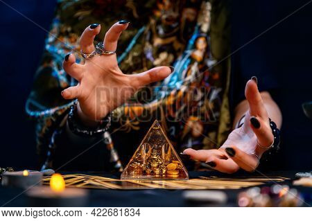 A Witch Is Guessing And Conjuring Over A Glass Pyramid. Hands Close-up. The Concept Of Divination An