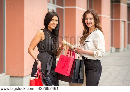 A Beautiful Young Woman Is Holding The Beige Shoe And Showing It To A Girlfriend Standing Near A Sho