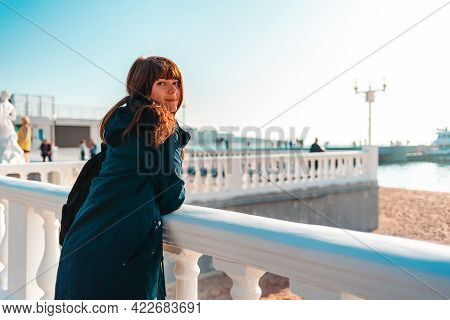 Vacation At The Sea. A Smiling Woman Leaning On A Balustrade And Looking At The Camera. Rear View. C