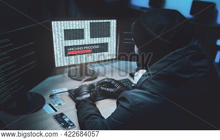 Shot From The Back To Hooded Hacker Breaking Into Corporate Data Servers From His Underground Hideou